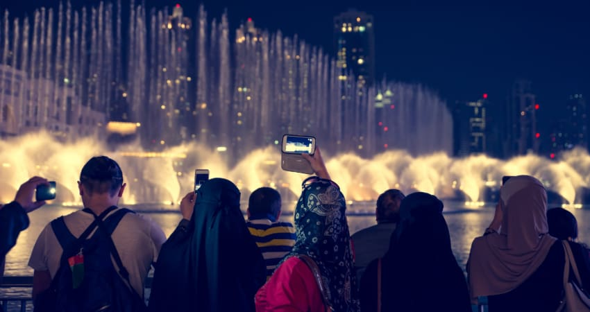 A group of visitors film the Bellagio Fountain nighttime water show on their smart phones