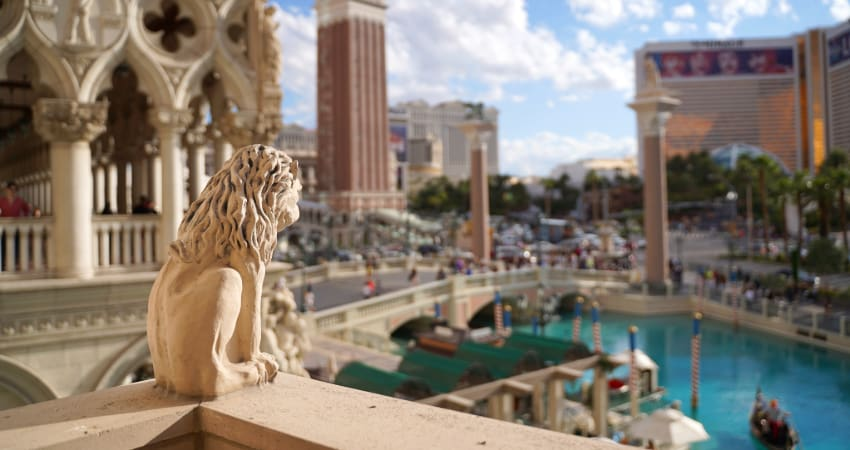 View from a balcony in the Caesar's Palace casino complex, with a sunny day and gondola canals visible in the background and a small gargoyle in the foreground