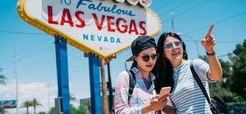 Two tourists in front of Las Vegas sign