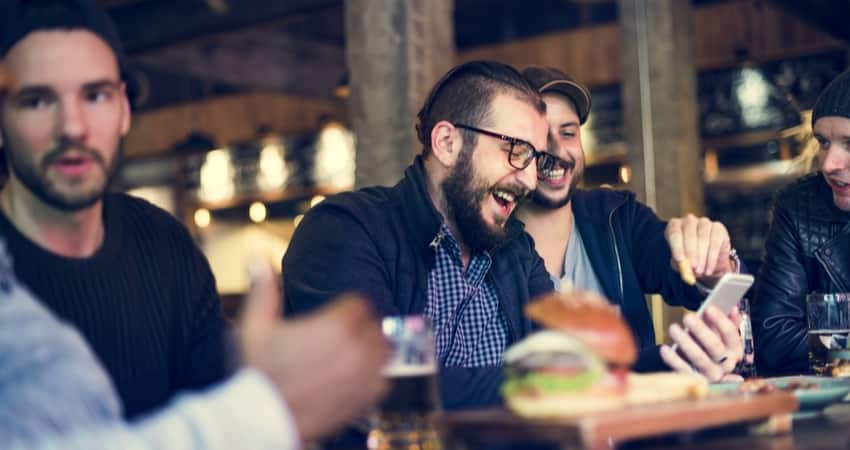 A group of friends laughing over burgers and beer at a bar