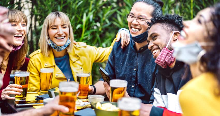 A group of friends laughing over beer on an outdoor patio