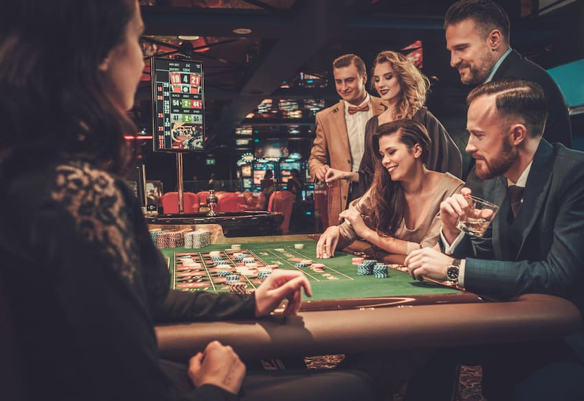 friends around a casino table game placing their bets