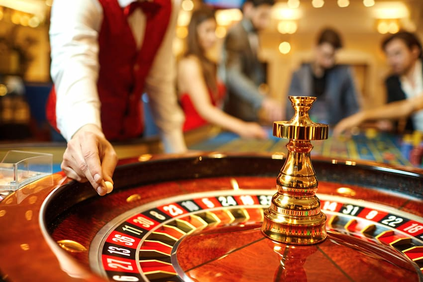 a casino employee gets ready to drop a roulette ball