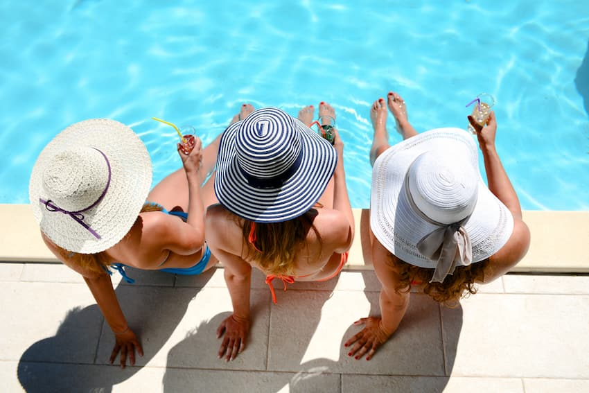 three friends with stylish hats sit by the pool with their feet in the water