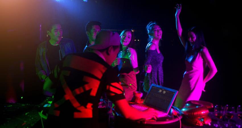 Dancers lit by rainbow light dance in a night club