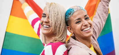 Two people painted in pride flag colors hold a rainbow flag and smile