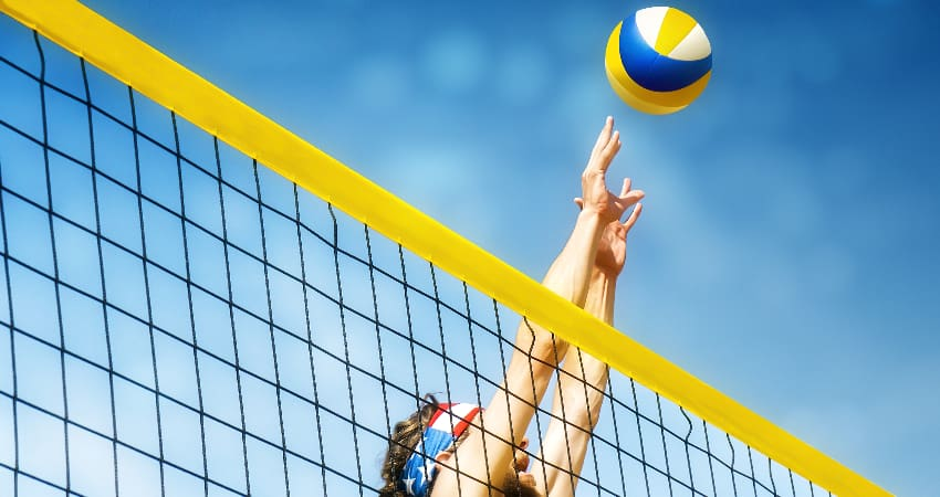 A volleyball player jumps to reach a ball flying over a net