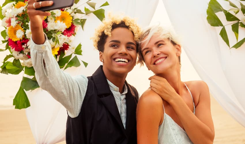 A happy lesbian couple smiles and takes a selfie on their wedding day
