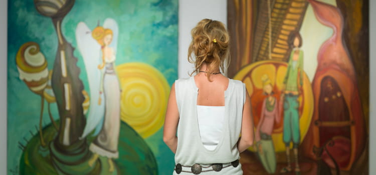 a woman looks at two art pieces in front of her