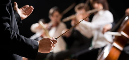 a conductor holds his baton in front of a string orchestra