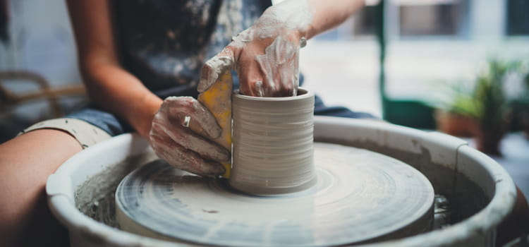 a woman shapes a pot on a pottery turntable