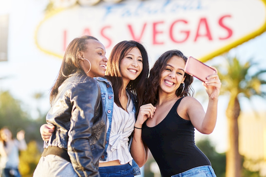 visitors pose for photo beside the Las Vegas welcome sign